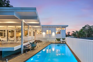 The family's pristine pool gleams under a pastel sky.