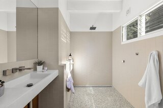 The neutral master bathroom with its terrazzo floor tiles.