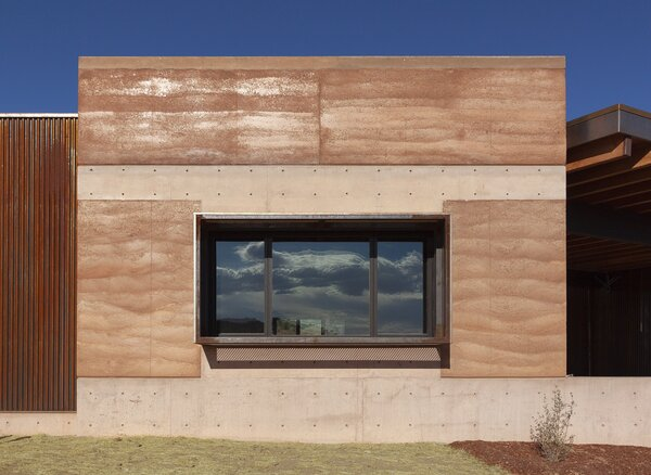 The facade of the home features rammed earth walls that were designed to blend in with the landscape.