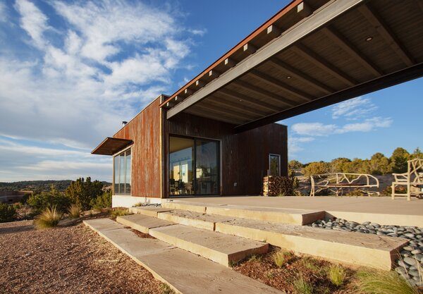 This view between the two casitas shows the compound's material palette, which includes stone steps, corrugated-metal siding, and steel detailing.