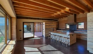 The kitchen, which connects to a spacious outdoor living area, features casework made from salvaged blue pine.