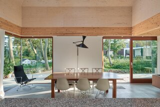 The corner window close to the dining table is now furnished with a comfortable chair where the couple spends time observing birds.