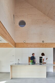 The open kitchen in the double-height space is a surprising experience once you enter the house. Two round peepholes were designed in the wall of the void, creating a visual connection between the kitchen and the upper floor.