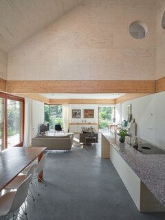 The airy interiors are finished with plasterboards and painted white while pine panelling warms the double-height space.