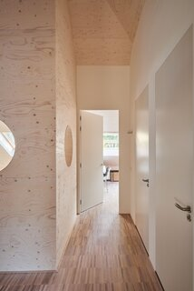 The  pine-cladded corridor on the upper level landing leads to the family's bedrooms.