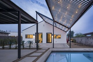 Large expansive steel shade trellis with bistro lighting just off the pool