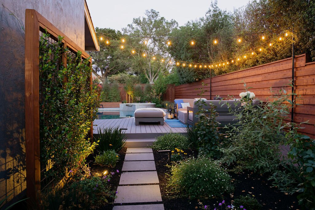 Outdoor, Back Yard, Garden, Horizontal Fences, Wall, Pavers Patio, Porch, Deck, Gardens, Flowers, Small Pools, Tubs, Shower, Small Patio, Porch, Deck, Hanging Lighting, Hardscapes, Walkways, Decking Patio, Porch, Deck, Post Lighting, Landscape Lighting, Trees, Shrubs, Wire Fences, Wall, and Wood Fences, Wall Bluestone step stones lead the way to the new entertaining space.  Modern Suburban Backyard