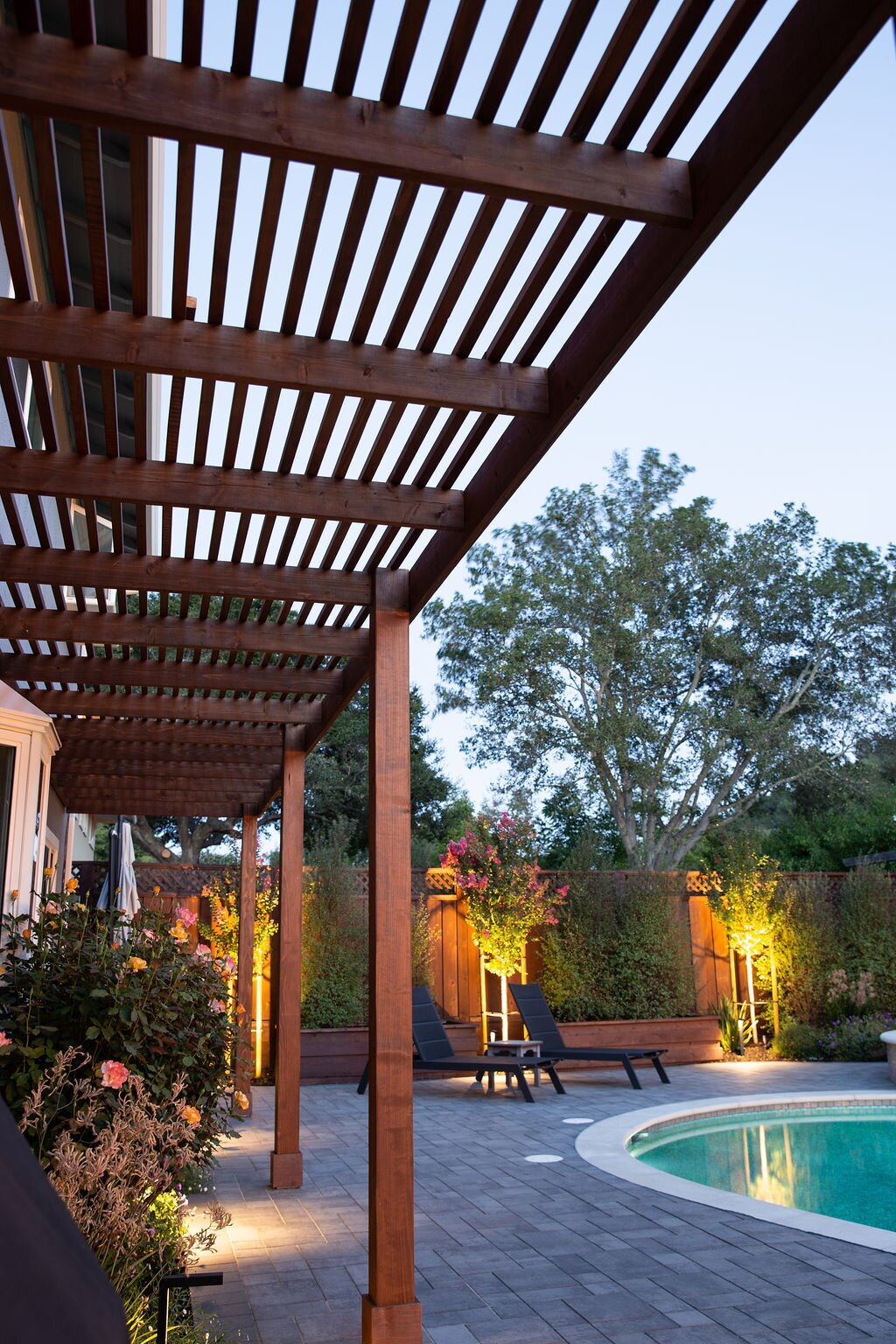 Outdoor, Shrubs, Back Yard, Hardscapes, Trees, Gardens, Garden, Pavers Patio, Porch, Deck, Small Patio, Porch, Deck, Small Pools, Tubs, Shower, and Landscape Lighting A new wood pergola provides shade to the house.  Modern Suburban Backyard