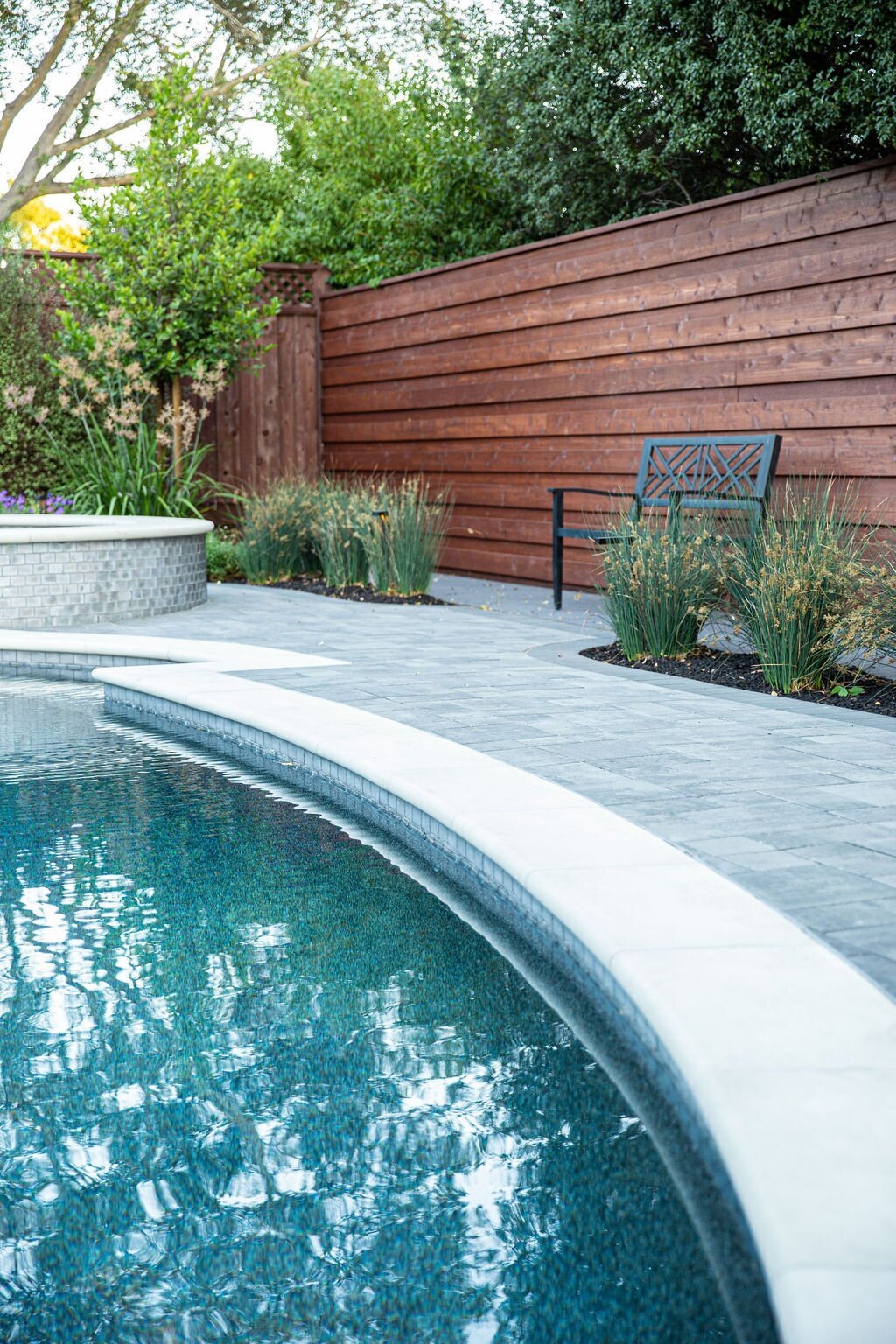 Outdoor, Back Yard, Small Pools, Tubs, Shower, Flowers, Shrubs, Hardscapes, Trees, Grass, Walkways, Gardens, Small Patio, Porch, Deck, Garden, Pavers Patio, Porch, Deck, Landscape Lighting, and Horizontal Fences, Wall Cohesion of materials.  Modern Suburban Backyard