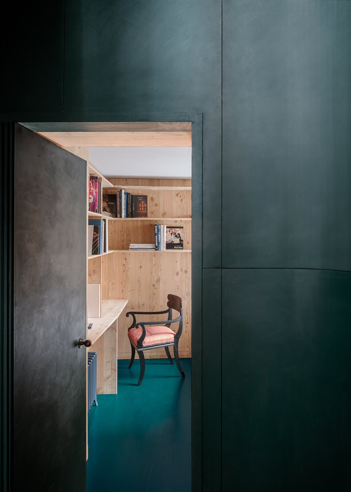 Office, Shelves, Desk, Medium Hardwood Floor, Chair, Storage, Library Room Type, Study Room Type, and Bookcase Curved green panelled joinery towards the study hideaway  Primrose Hill