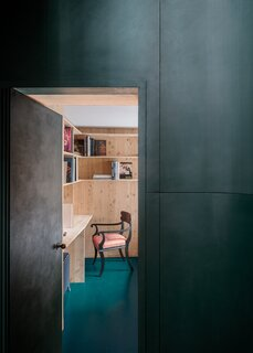 Curved green panelled joinery towards the study hideaway