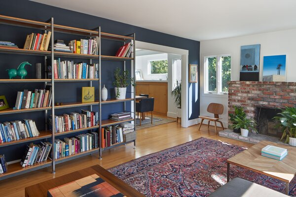 "The living room's steel-framed bookcase, with cherry shelves, is a custom design by the architect. ""The floor was so uneven, I knew the feet had to be adjustable,"" says Rudabeh. The wall behind them is painted in Benjamin Moore's Hale Navy, and the other walls are painted in Benjamin Moore's Chantilly Lace. The popcorn was scraped off the ceiling and replaced with a thin coat of plaster."