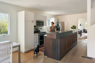 Simple, white IKEA cabinetry allows the Henrybuilt walnut island, a secondhand find, to be the star of the kitchen.