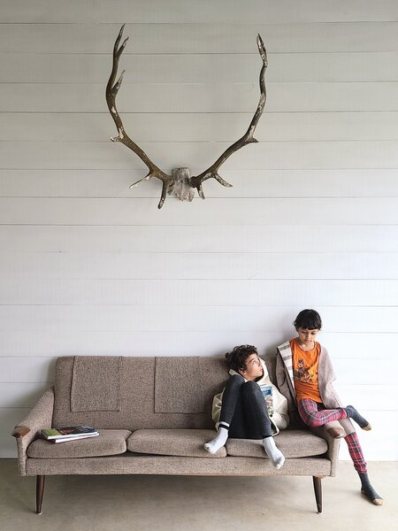 In the porch room, Max, 10; and Emily, 8, sit on a vintage sofa from Gone Vintage in Belleville, Ontario. The caribou antlers are from Aberfoyle Antique Market in Puslinch, Ontario.