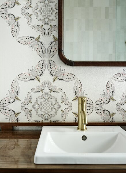 The main bathroom features Timorous Beasties' White Moth Circle wallpaper. The mirror and vanity are from Gone Vintage in Belleville, Ontario. The shower is tiled in white saltillo tile from Saltillo Imports in Toronto.