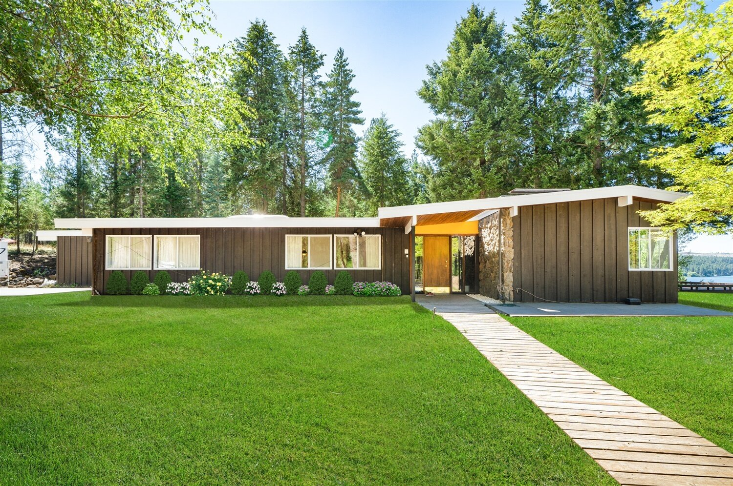 Exterior, Flat RoofLine, Mid-Century Building Type, Wood Siding Material, House Building Type, and Metal Roof Material The landmarked midcentury residence just outside Spokane, Washington, features a massive lava-rock fireplace and a cedar-wrapped solarium.  Photo 1 of 15 in Moritz Kundig's Historic Wallmark House Offers Lakefront Living for $1.1M from The Wallmark House by Moritz Kundig