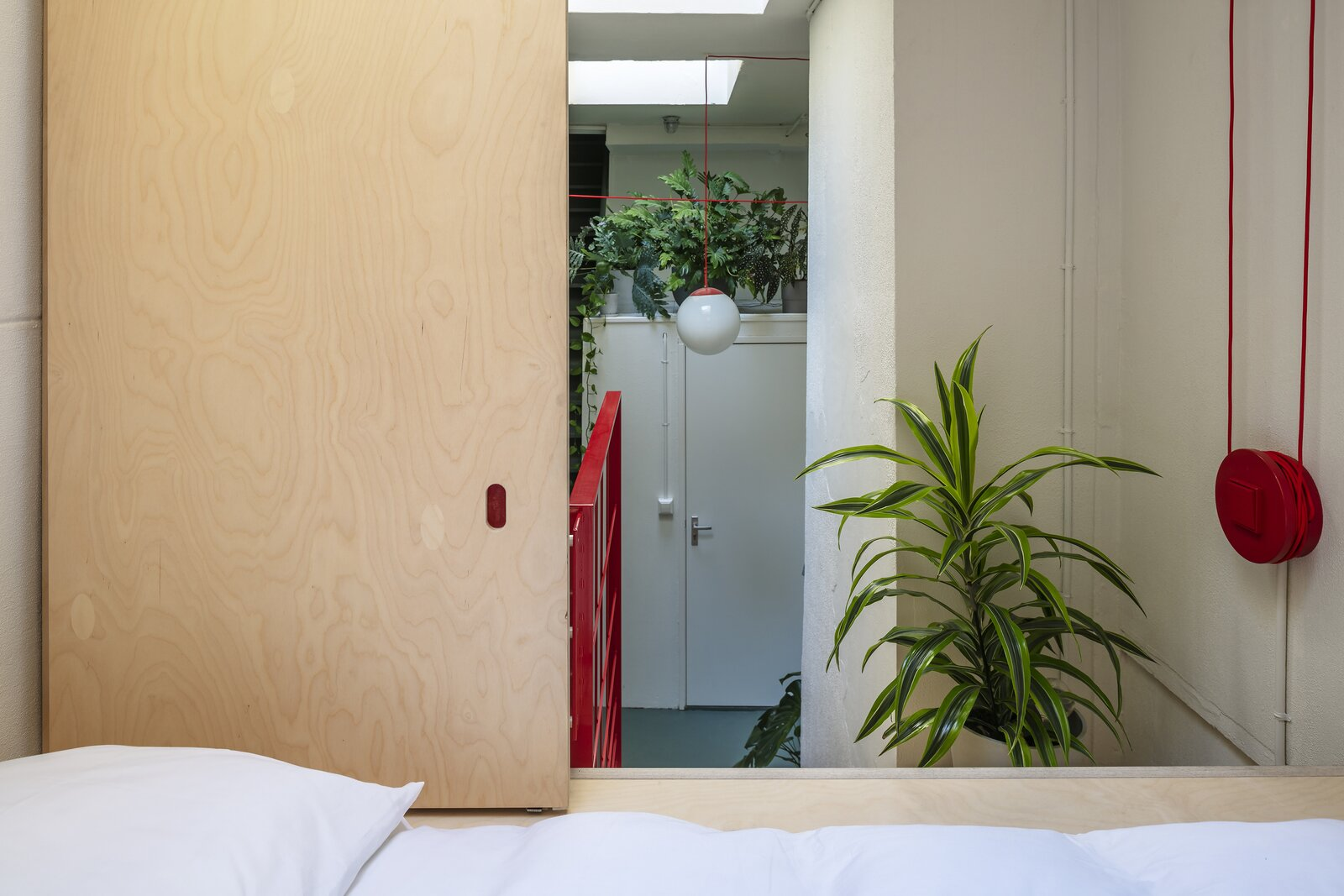 Bedroom, Night Stands, Concrete Floor, Ceiling Lighting, Bed, Plywood Floor, and Pendant Lighting inside the cocoon - a contemporary cupboard-bed  Silence in the city – A cocoon in Amsterdam's Canal District by Équipe Amsterdam