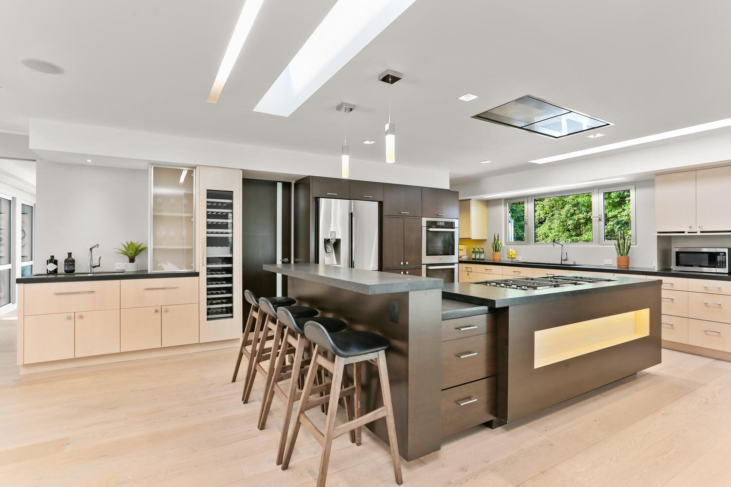 Modern home with Kitchen, Refrigerator, Granite Counter, Ceiling Lighting, and Cooktops. Kitchen with Skylight  Photo 15 of A Gut Renovated MidCentury Modern Green Energy Home for Luxury Winter Living for $4.65m