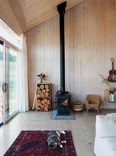 The restrained 820-square-foot interior is defined by the angular ceiling. Garlick left the prefabricated structural panels unfinished to save on material costs. A True North wood stove from Pacific Energy heats the house. Max, the family's cat, naps on a vintage rug purchased on eBay.<br>