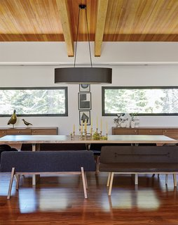 A wood slab table is paired with bench seats from De La Espada and a vintage brass candelabrum in a family home near Lake Tahoe. The credenzas are Bo Concept. An oversize oval black linen shade from Dogfork Lamp Arts hangs above a table Maca created out of a wood slab from West Marin-based artisan Evan Shively of Arborica. The brass candelabrum is vintage, sourced from 1stDibs.