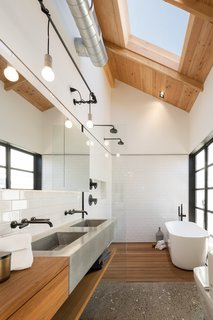 A skylight illuminates the neutral palette of this master bathroom, letting bathers peacefully contemplate the clouds from the privacy of its enclosed walls. The wood counter, concrete sink, and pebbled floor create a calming, textured space, and the natural materials stand out against the white subway tile.