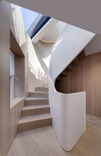 On a triangular site in the Fitzrovia neighborhood of London, architecture firm FORMstudio created an irregularly shaped stair with treads and risers that match the wide-planked, white oak floors. A thick acrylic banister winds alongside the stair like a matte-white ribbon. Together, the white oak and acrylic have a distinctly calm, Scandinavian feel about them.