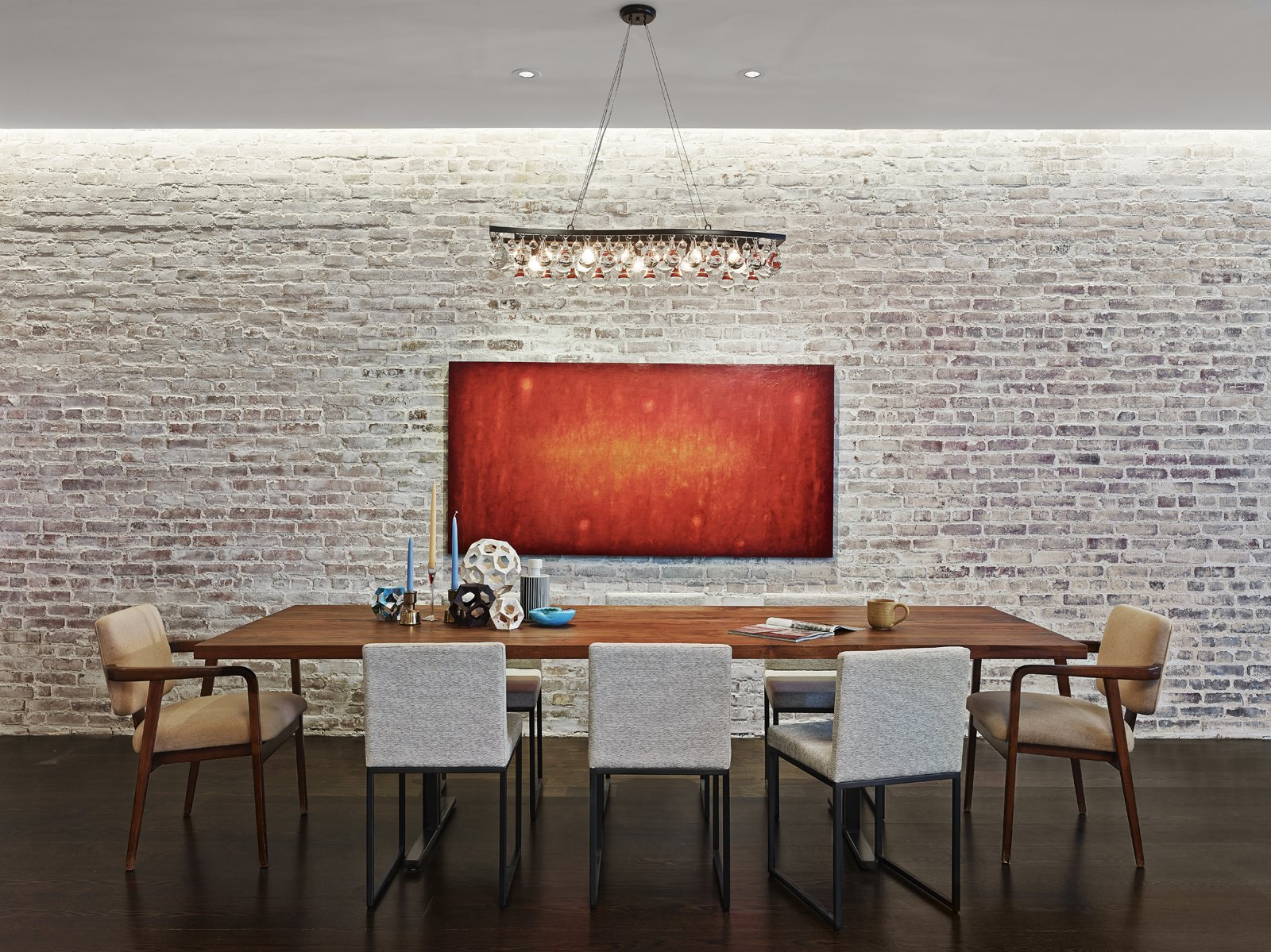 """The brick wall adjacent to the custom dining table by Brooklyn-based Uhuru Design is original to the structure. 590BC and its team spent months trying to find the right translucency for the whitewash covering the brick. """"We call it the 'selective loft' because of the contrast of the refined materials and cabinetry against the industrial materials of this former light bulb factory,"""" says Breitner. Photo by Frank Oudeman.  Photo 7 of 10 in Revealing the Pros and Cons of Exposed Brick and How to Take Care of It from A Renovated Loft in SoHo"""