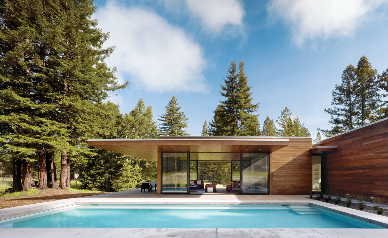 Large Pools, Tubs, Shower, Concrete Pools, Tubs, Shower, Swimming Pools, Tubs, Shower, Large Patio, Porch, Deck, Concrete Patio, Porch, Deck, Exterior, House Building Type, and Wood Siding Material Two linked 1,000-square-foot pavilions are greater than a sum of their parts. The simply detailed, taut, flat-roofed home's two wings form a T-shape. One wing runs north to south, parallel to a pool, and contains the open-plan living spaces. Photo by Matthew Millman.  Photo 1 of 5 in This Couple Achieves Their Glass House Goals