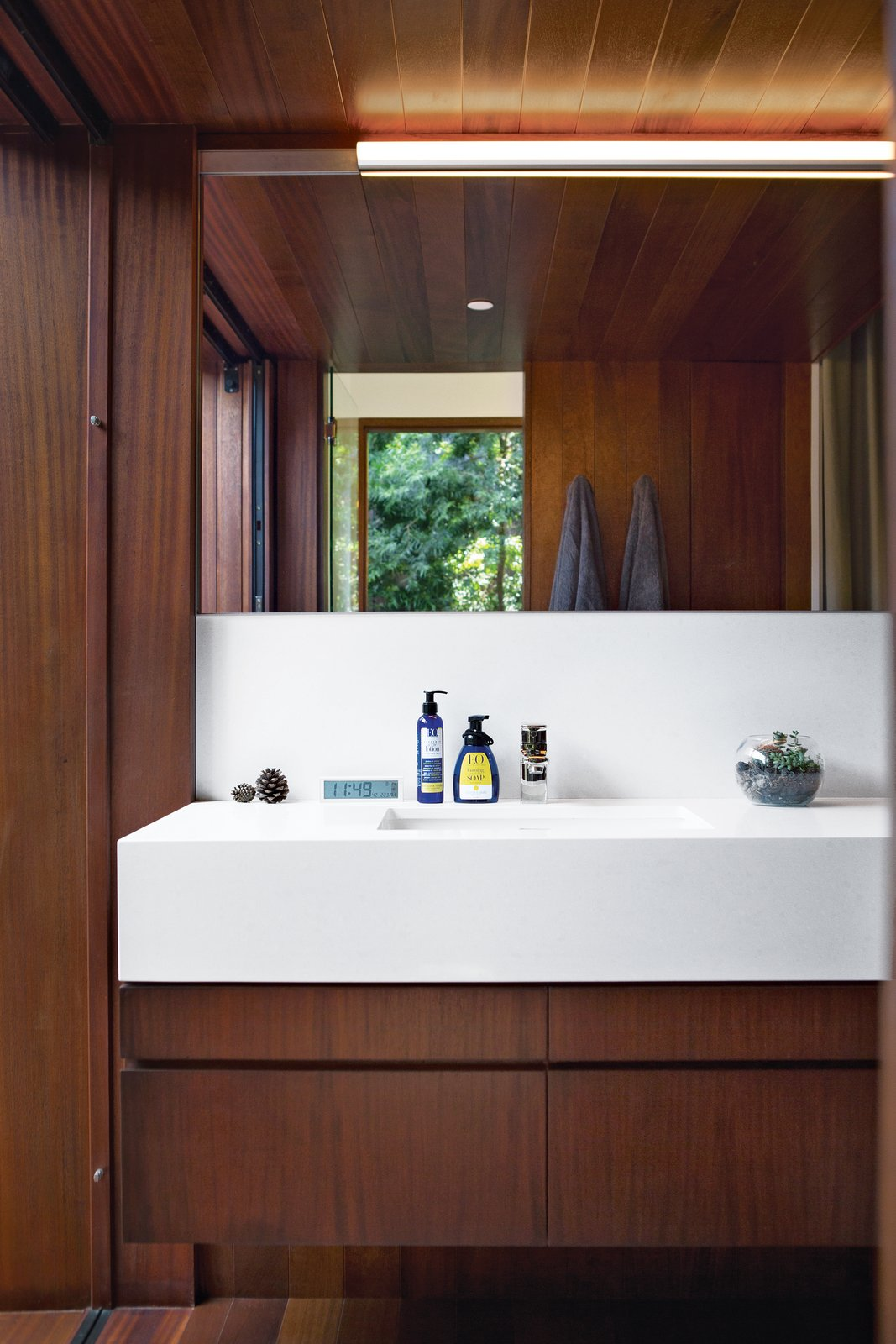 Bath Room, Accent Lighting, and Undermount Sink The couple chose to contrast the wood in the master bath with a smooth Caesarstone counter in Organic   White 4600, which was measured and cut specifically for the space. They added a bit of shine with polished-nickel Upton fixtures from Toto. Photo by Coral von Zumwalt.  Photo 9 of 10 in A Modern Bungalow in Venice Beach