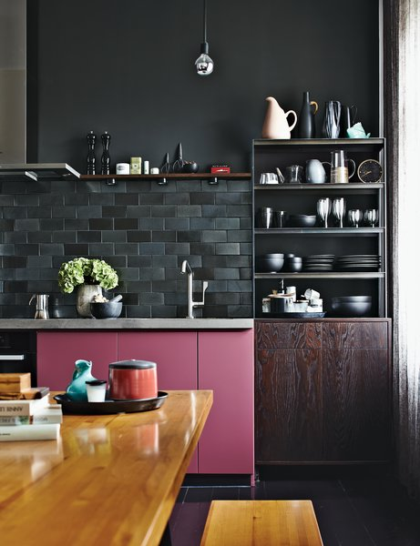 In a moody apartment in Berlin, multi-toned charcoal gray subway tiles make up the backsplash, which contrasts with the pop of rosy color on the kitchen cabinets. The pink is a custom hue.