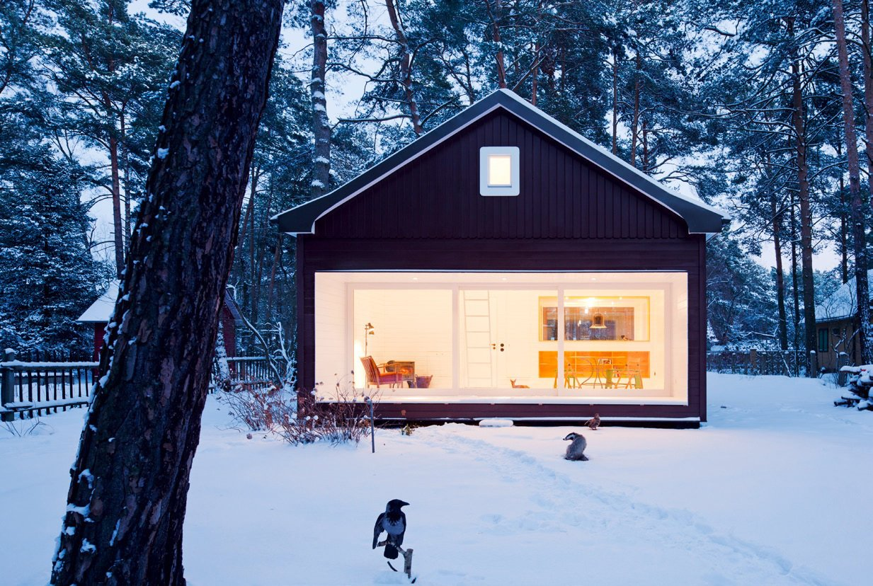 Exterior, Glass Siding Material, Cabin Building Type, House Building Type, Wood Siding Material, Small Home Building Type, and Gable RoofLine Choosing not to make a big to-do of itself, this cottage blends in with its surroundings. A wall of glass on one end allows a merger of the outdoors with the interiors, while white trim leaves the appearance of a snow-kissed façade year-round. Berlin, Germany. By Atelier st Gesellschaft von Architekten mbH  from the book Rock the Shack, Copyright Gestalten 2013.  Photo 31 of 101 in 101 Best Modern Cabins from Modern A-Frame Homes