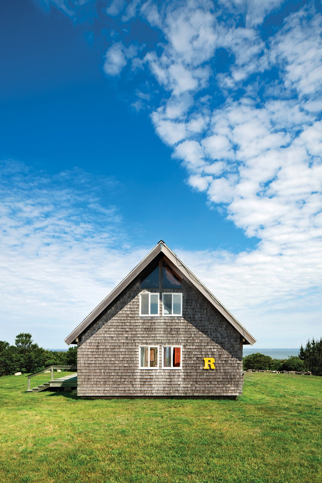 "A bright-yellow ""R"" sign, from a truck that used to deliver furniture from Jens Risom Design, sets off the southern facade. When Jens designed the house, he stipulated that he wanted cedar shingles, not the asphalt ones that came with the original design from the catalog. Tagged: Exterior, Shingles Roof Material, House, Wood Siding Material, Cabin Building Type, Gable RoofLine, A-Frame RoofLine, and Prefab Building Type.  Photo 12 of 13 in Jens Risom's Block Island Family Retreat"