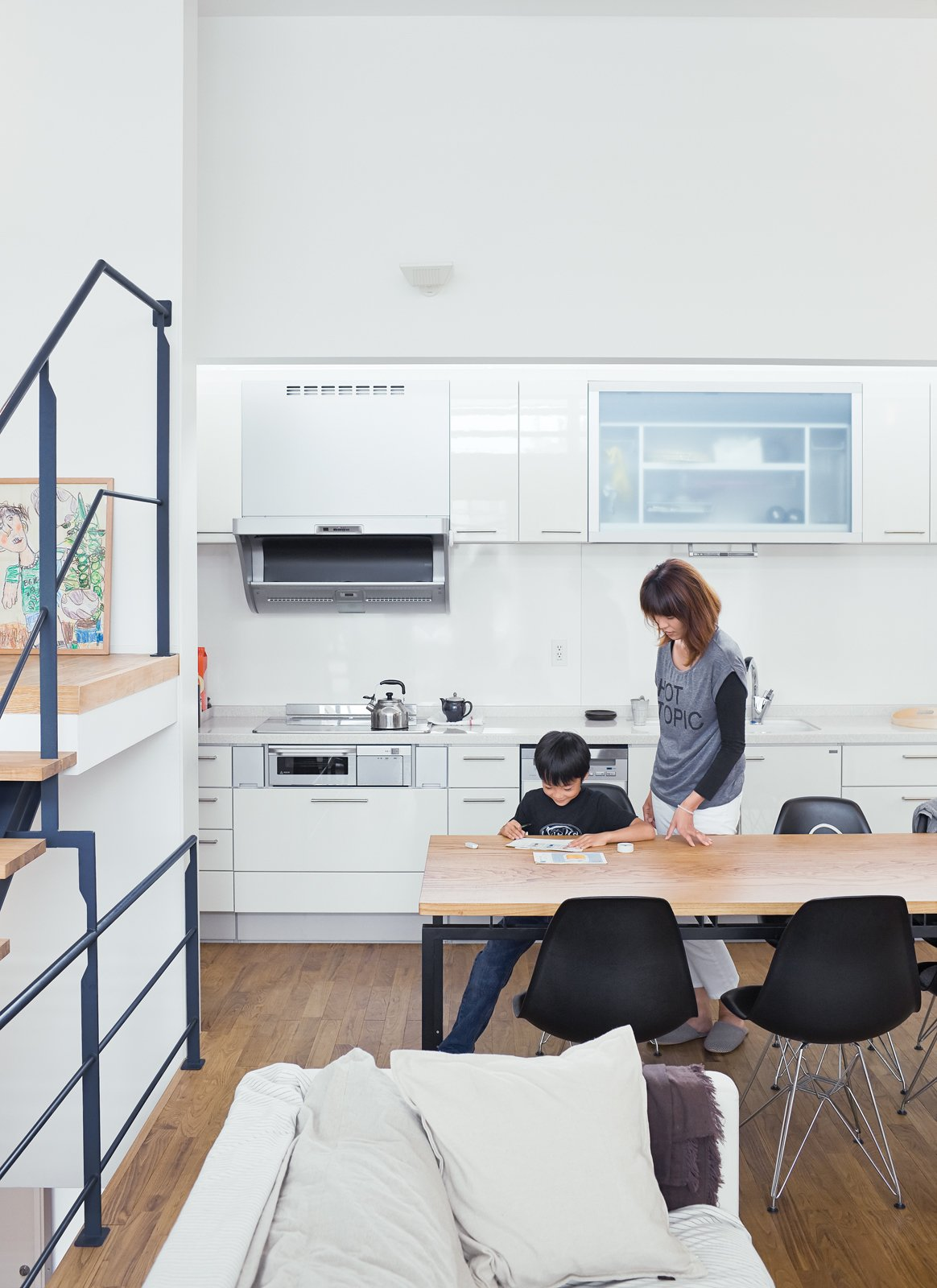 """White Cabinet, Dining Room, Chair, and Table Called the """"LDK,"""" for living, dining, and kitchen, the space is flexible—a blend of Western loft life and traditional Japanese homes, where rooms are multipurpose.  Photo 5 of 14 in Small Box Home with Black Metal Facade in Japan"""