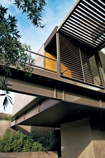 The modular two-story steel-and-glass structure sits atop a windy ridge on the city's western edge, near Red Rock Canyon. Its prefabricated components—steel-frame modules that were prepared with finished floors, walls, doors, and fenestration, or were designed as canopied or trellised decks—were all made in Marmol Radziner's home-building factory, near Los Angeles, and trucked over to the one-and-a-half-acre site.