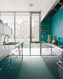 A mosaic tile wall softens the laboratory-like effect of the glossy kitchen cabinets.