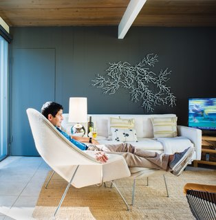 """See for Yourself<br><br>After painting the sitting room room Kendall Charcoal from Benjamin Moore's Aura line, Neely wanted a sculptural element that would show up against the dark hue. So he assembled his white Algues set, designed by the Bouroullec brothers for Vitra, on the wall behind the sofa with pillow by Judy Ross. """"Though the Bouroullec piece is manufactured in mass quantities, you can create your own take on it,"""" he says. """"It looks great no matter how you place it. I think of it almost like an inkblot—the randomness is part of its beauty."""""""