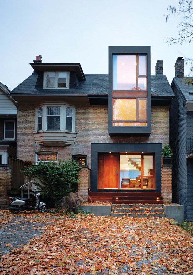 Exterior, Metal Siding Material, House Building Type, and Brick Siding Material Mandel mounted the fireplace in a blackened-steel frame, which echoes the window and door treatment on the house's new facade.  Photo 1 of 5 in Reinventing a Traditional Edwardian near Lake Ontario