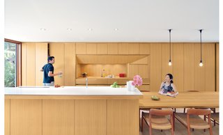 "For a Toronto couple with a love of minimalist Japanese architecture, a sleek, storage-packed kitchen was the first priority in their home's renovation. In the kitchen, white oak used for the cabinets, kitchen island, and dining table is finished with double-boiled linseed oil, which can be reapplied by the homeowners as the wood mellows and patinas. The custom beveled edge for the island's ""Blizzard"" white Caesarstone countertop forgoes the standard one-inch countertop overhang to save on space and maintain a sleek feel. A Vola faucet is used with a sink by Mekal."