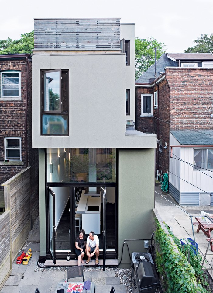 Outdoor, Back Yard, Walkways, Hardscapes, Horizontal Fences, Wall, Wood Fences, Wall, and Stone Patio, Porch, Deck A rear view of the narrow house shows how Chong twisted the house's volumes to bring daylight into each room.  Photo 16 of 18 in Narrow Modernist Three-Story Home in Toronto