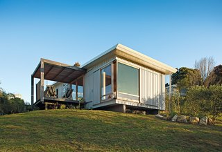 A compact prefab vacation home in the seaside community of Onemana Beach is clad in plywood and vertical timber battens finished in Resene's Lumbersider paint.