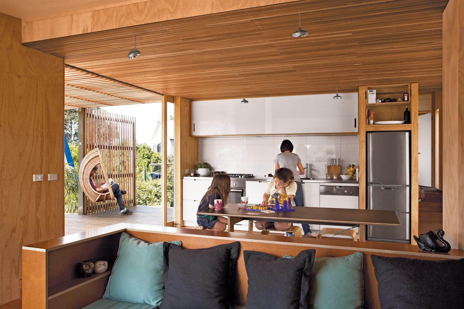 A dishwasher by Miele, refrigerator by Mitsubishi, and Baumatic cooktop are nestled into the custom kitchen, which features laminate-covered cabinets and a stainless steel countertop.  Photo 4 of 7 in A Compact Prefab Vacation Home