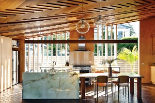 "In the kitchen, the showstopping ceiling's herringbone pattern is echoed by the terra-cotta tiles on the floor. Architect Michael O'Sullivan, who designed the steel-and-glass kitchen cabinets, the table, and the pendant lights (made by Lava Glass), further amped up the richness of the room by specifying an onyx kitchen island. Interior designer Yvette Jay, a collaborator and classmate of O'Sullivan, kept her material palette ""tight and limited. I had to restrict myself so that everything here ties in with the architecture."""