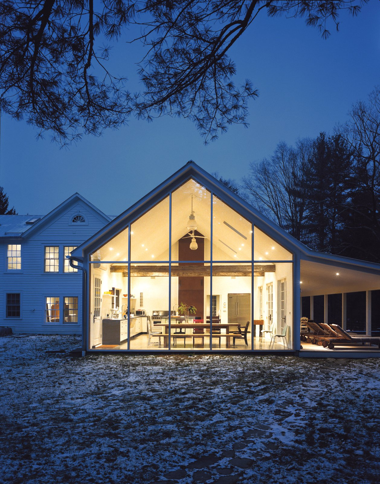Exterior, House Building Type, Farmhouse Building Type, Gable RoofLine, and Glass Siding Material The Floating Farmhouse's semitransparent addition has a roofline that matches the pitch of the original 1820s farmhouse. A porch, tucked under the side eaves, is cantilevered over a stream that runs through the property. Ikea loungers are illuminated from the interior by commercial gymnasium lights repurposed as pendant lamps.  Photo 8 of 12 in Hope Floats