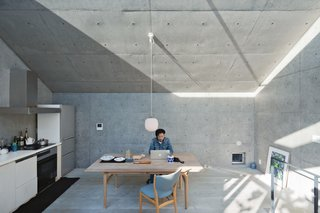 Nakada works from an Alvar Aalto table in the living and dining area, adjacent to the kitchen. He saved on some elements, such as the plywood cabinetry, and splurged on others, such as the Finn Juhl chairs and Vilhelm Lauritzen lamp. A skylight beneath the angled roof allows in a sliver of constantly changing light.