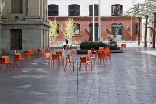 Mint Plaza in San Francisco used to be a highly sketchy back alley. Today it's a vibrant public pedestrian plaza and festival space lined with restaurants and cafes, filled with dozens of movable bright orange chairs and shaded by a vine-covered steel trellis.