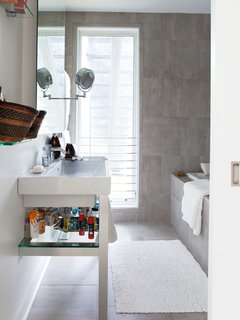Early on in the design process, Church had to forgo her fantasy of concrete floors with radiant heat and a cast-concrete sink. But her gray-tiled bathroom satisfies her concrete-loving aesthetic at a much lower price point.