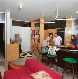 The resident of this home wanted to be able to use the space as a fun gathering place for parties, so Bestor set a DJ booth at the edge of the kitchen. Custom plywood shelving holds vinyl records.