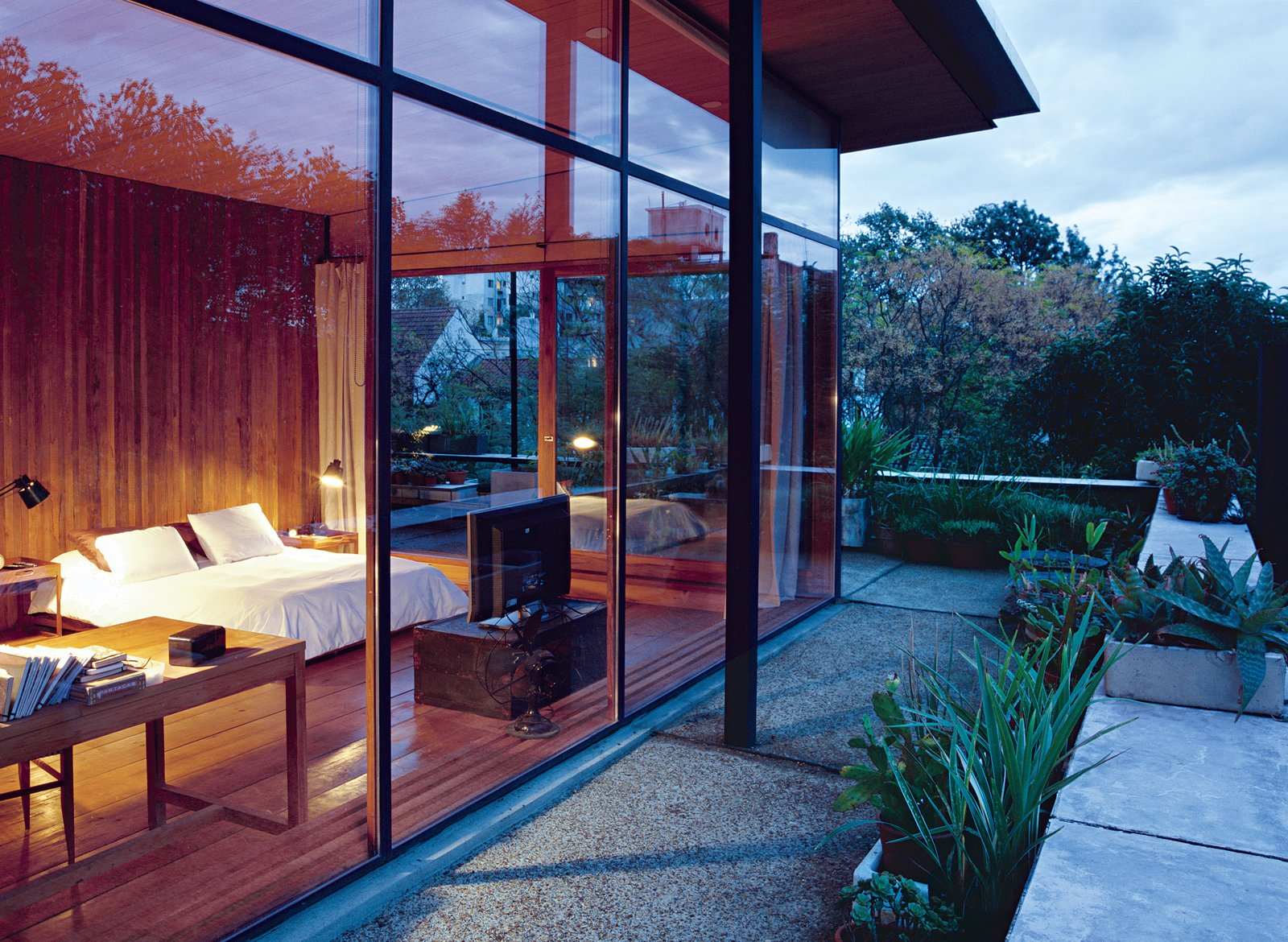 Bedroom and Bed Dappled sunlight and reclaimed-wood floors and walls give the master bedroom a warm, peaceful feel. Giant sliding doors open onto a wraparound deck peppered with potted plants   from the couple's vacations in Brazil, Uruguay, the Netherlands, and Italy.  Photo 7 of 12 in 10 Examples of Sustainability at Work in Outdoor Spaces from Net Assets