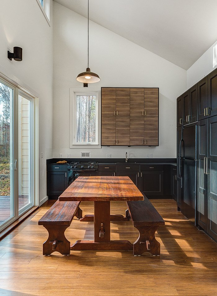 "To keep costs down elsewhere (the house was built for just over $118,000), architect Brun and his partner Lizmarie Esparza specified Ikea kitchen cabinets and a black refrigerator, which is less expensive than stainless steel. ""It was really important that the kitchen opened up to the outside deck. Its designed in an L-shape with an indoor-outdoor table,"" Brun says. ""The idea is that when you open the door, there's a continuous environment connecting the inside with the outside—it's as open as possible."" Gordon purchased the hand-crafted solid teak antique table from Indonesia.  Photo 2 of 6 in How to Build an Off-the-Grid Cabin in Arkansas for just over $118,000"
