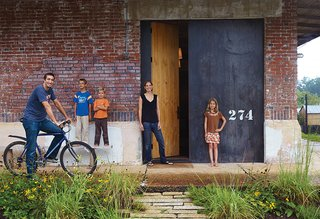 Architect David Hill, his wife, Elizabeth, and their three children (from left: Wade, eight; Luke, six; and Breyton, ten), have an unusual home by the standards of their college-town setting in Auburn, Alabama. Built in 1920, the industrial brick building has had previous incarnations as a church, a recycling center, and a pool hall, among others.
